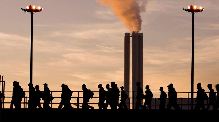 Factory workers silhouetted against evening sky