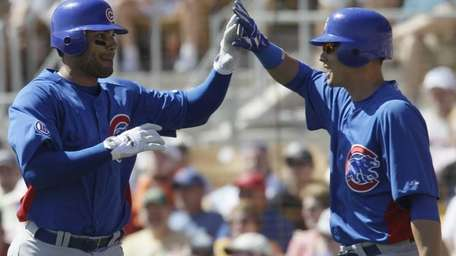 Chicago Cubs' Carlos Pena, left, celebrates with teammate