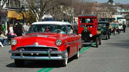 Classic cars drive down Main Street during the