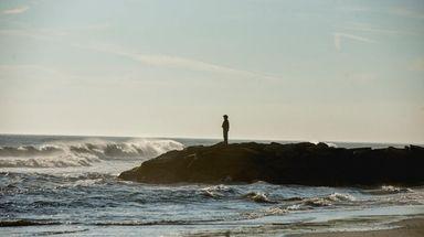 A beachgoer stands watch Thursday over the Atlantic