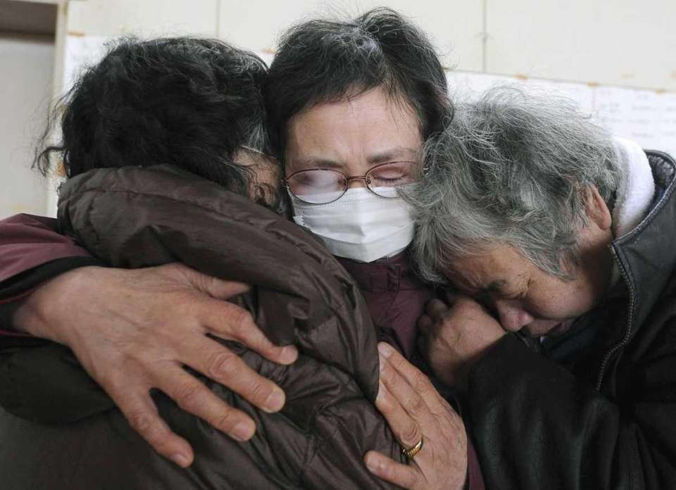 Women mourn at an evacuation center in Kesennuma