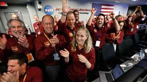Engineers from the flight team react at NASA's