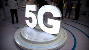Visitors stand near a 5G logo at a