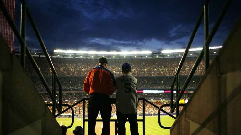 A young fan and a Mets employee watch