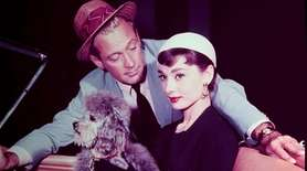 Audrey Hepburn holds a poodle as William Holden