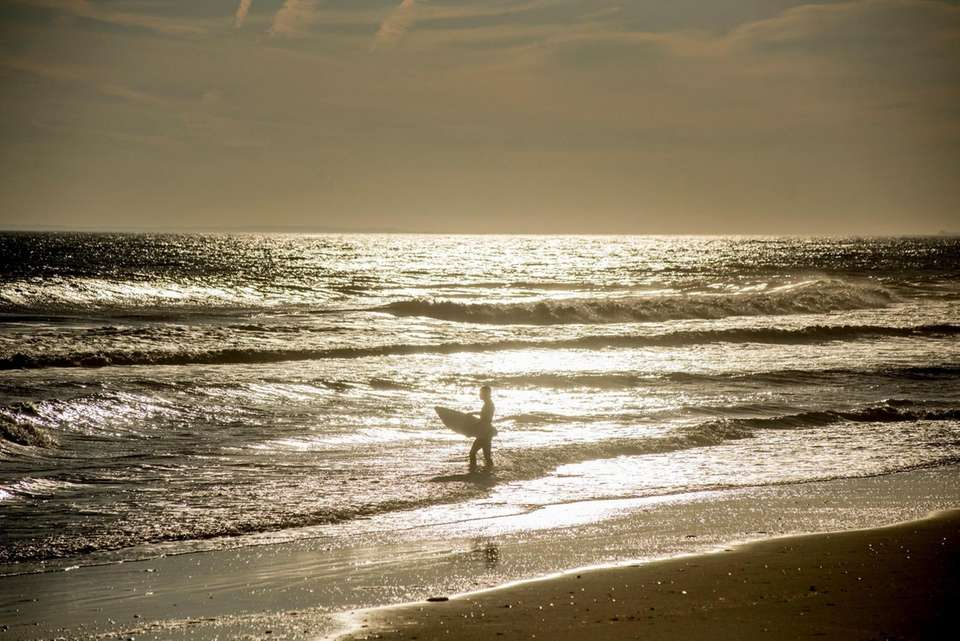 A surfer wades into the Atlantic Ocean off