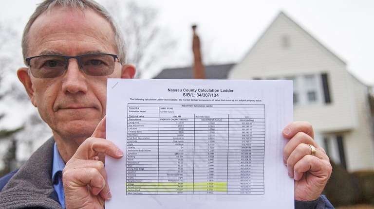 Dan Oppenheimer holds a report on his property