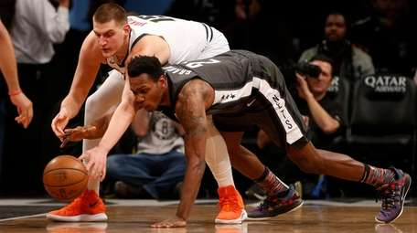 Treveon Graham of the Nets reaches for the