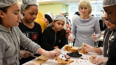Mentor Sunday Caldwell, center, helps her students from