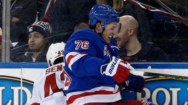 Brady Skjei of the Rangers checks Brett Seney