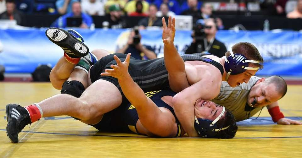 Angelo Petrakis of Massapequa wrestles Jake Logan of