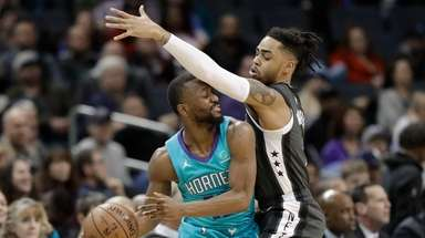 The Hornets' Kemba Walker, left, is fouled by
