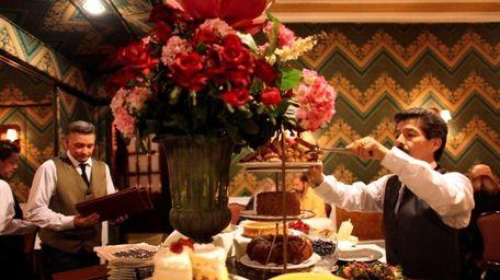 A waiter serves a portion from the dessert