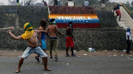 Venezuelan demonstrators throw stones during clashes with authorities,