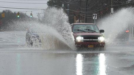 Vehicles drive through flooding on Horseblock Road at
