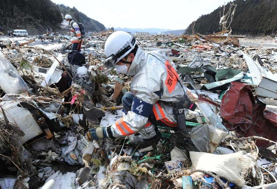 Rescue workers search through debris in Minamisanriku, Miyagi