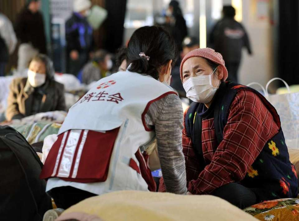 An evacuee, right, is checked by a doctor