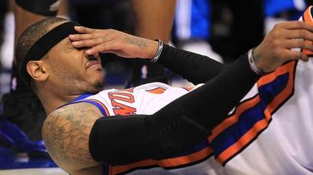 The Knicks' Carmelo Anthony reacts after falling out