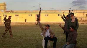 Libyan government soldiers wave at foreign journalists at