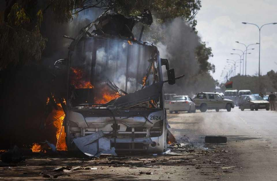 A bus burns on a road leading to
