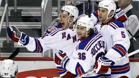 The Rangers' Ryan Callahan, left, celebrates with teammates