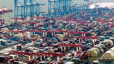 Trucks move around containers stored at a port