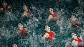 Swimmers perform in a synchronized swimming gala event