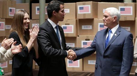 Venezuelan opposition leader Juan Guaidó shakes hands Monday