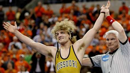 Missouri's Ben Askren celebrates after beating Northwestern's Jake