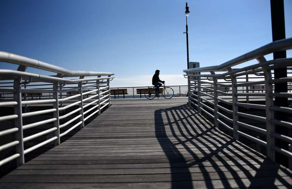 A biker rides along the boardwalk in Long