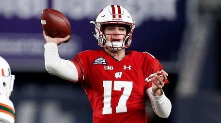 Wisconsin quarterback Jack Coan passes under pressure from