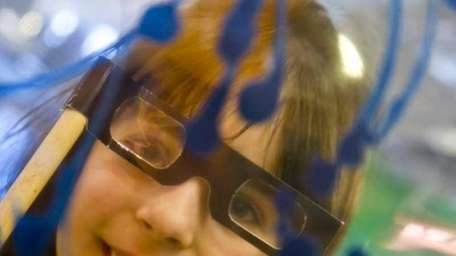 Brianna Reese, 7, uses 3-D glasses to view