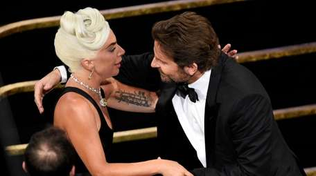 Bradley Cooper, right, congratulates Lady Gaga for winning