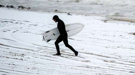 A surfer in Long Beachleaves the snowy beach