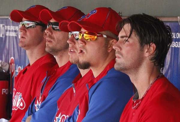 Philadelphia Phillies pitcher Cole Hamels, right, sits in