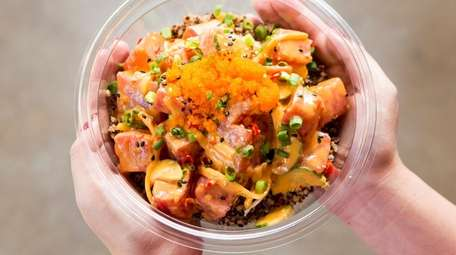 A spicy ahi tuna poke bowl is on