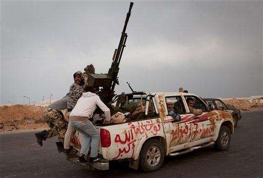 Libyan rebels jump onto the back of their