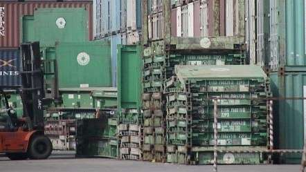 A forklift arranges the shipping containers near a