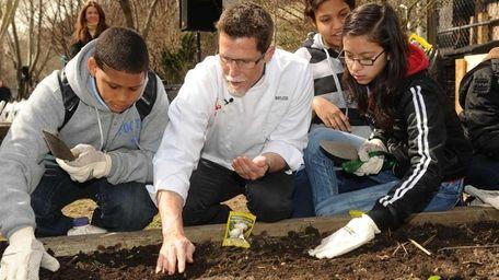 Celebrity chef Rick Bayless, center, plants Seeds of