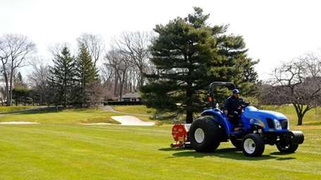 Eliseo Lopez uses a Verti-Drain machine on the