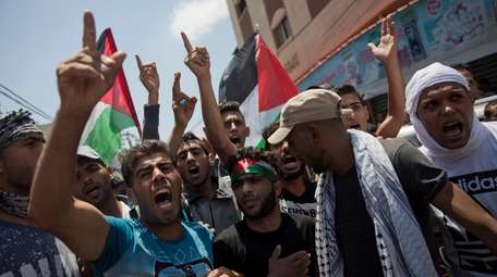 Palestinians protest during the funeral of volunteer paramedic,