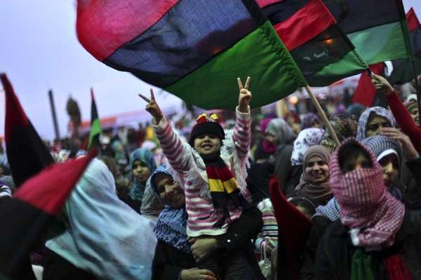A girl flashes a victory sign as women