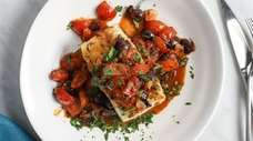 Pesto-crusted Chilean sea bass with tomatoes and risotto