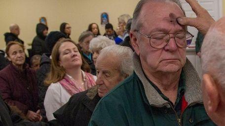 John Patterson, Westbury, receives ash as he prays