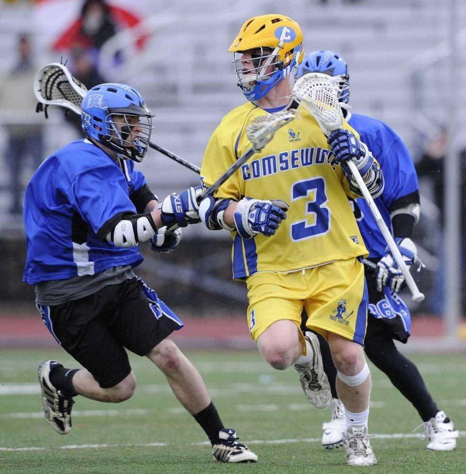 Comsewogue's Ryan Brunet drives through Hauppauge defenders in