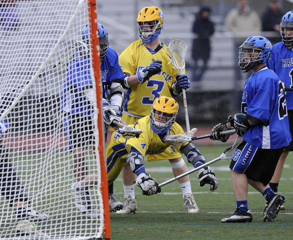 Comsewogue's Conor Russell, bottom center, takes a shot