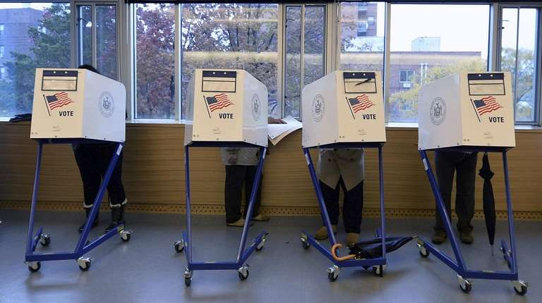 Voters fill out their ballots inside the Queens