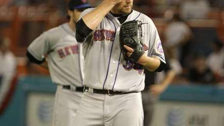 The Mets' Mike Pelfrey wipes his face during