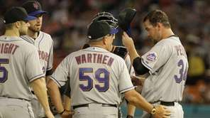 The Mets' Mike Pelfrey, right, talks to pitching