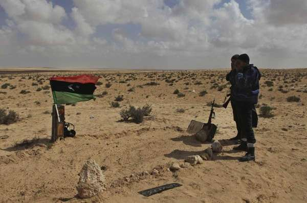 Libyan rebels pray near the a graves of